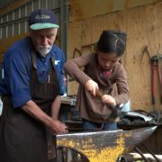 Mila and Peter blacksmithing